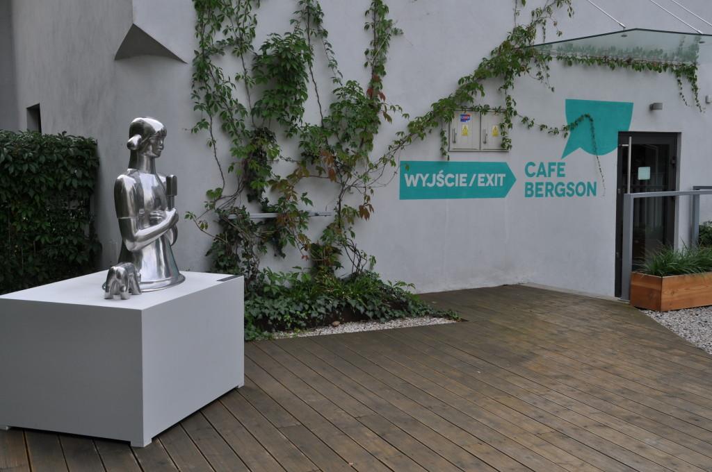 Piesek chłepczący kałużę, którą staje się dziewczynka topniejąca pragnieniem zjedzenia loda, 97x85 cm, aluminium, 2013; Cafe Bergson, Oświęcim