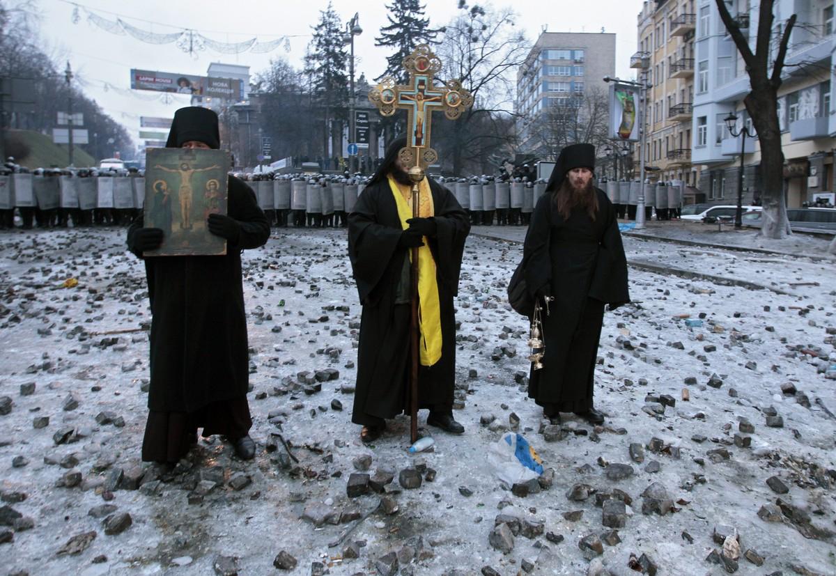 Duchowni prawosławni stojący pomiędzy policją a pro-europejskimi demonstrantami, Ukraina, 2014, (AP Foto/Sergei Chuzavkov)