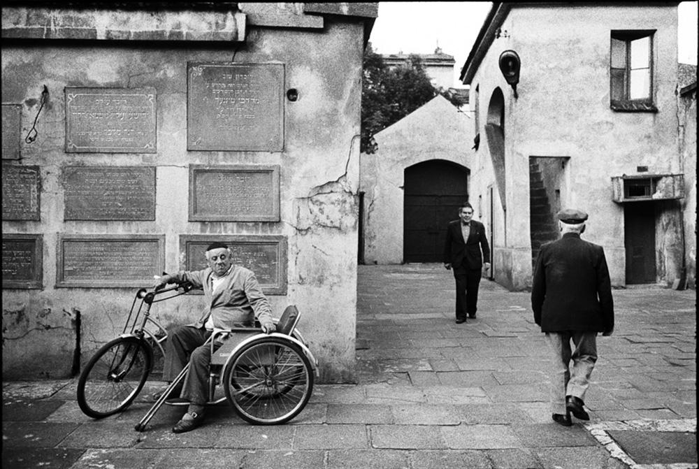 W drodze na piątkowe wieczorne nabożeństwo. Na dziedzińcu krakowskiej synagogi Remu. Pan Lemper w swoim tri-cyklu. 1983, fot. Chuck Fishman